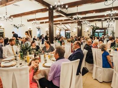 Goście przy stołach na weselu